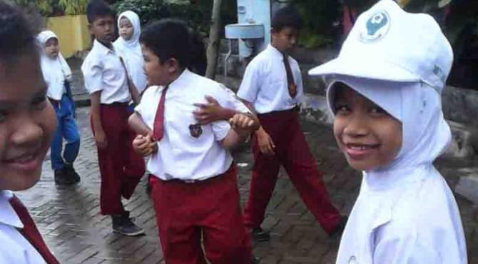 Aisyah (kanan) saat berm,ain dengan teman sekolahnya di SD Negeri 20 Indarung beberapa waktu lalu.
