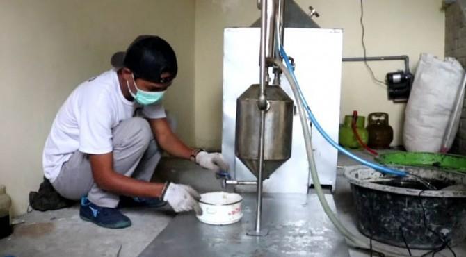 Sisra Ismail saat mengolah sampah plastik menjadi BBM di Pessel