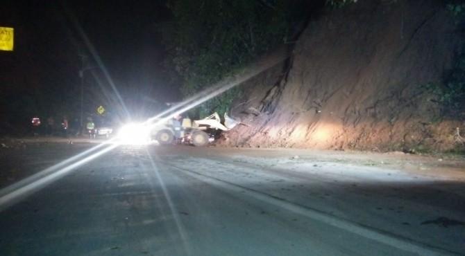 Allat berat sari Dinas PU tengah membersihkan material longsor di Jalan Padang-Solok