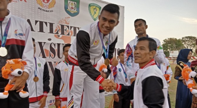 Ketua KONI Sumbar mengalungkan medali kepada Yaspi Bobby yang turun di nomor estafet