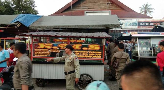 Petugas gabungan menyita gerobak sate yang diduga mengandung daging babi di kawasan Simpang Haru, Padang.