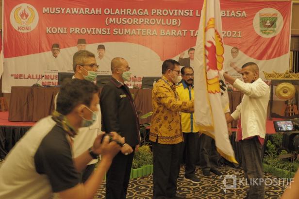 Agus Suardi menerima bendera pataka KONI dari pimpinan sidang, Syahrial Bakhtiar