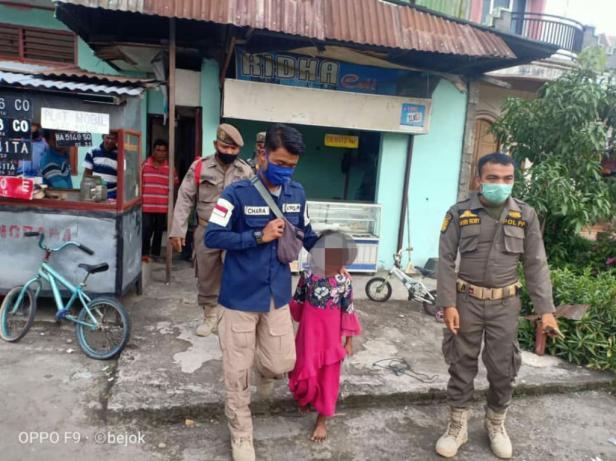 Personel Satpol PP Padang membawa anak yang terlantar di perempatan jalan di Kota Padang