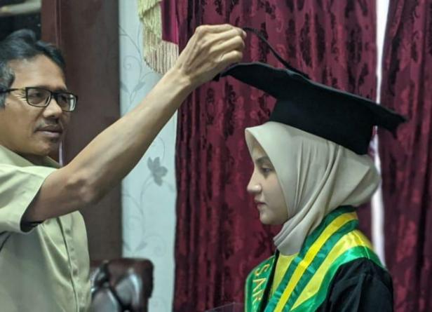 Gubernur Sumbar Irwan Prayitno saat memindahkan jambul toga wisuda anaknya