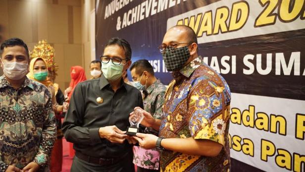 Gubernur Sumbar Irwan Prayitno (kiri) menyerahkan tropy anugerah Achievement Motivation Person Award 2020 dari Komisi Informasi Sumbar kepada Andre Rosiade (kanan)