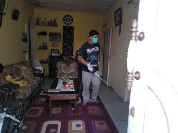Salah seorang anggota Karang Taruna REKOTA tengah lakukan penyemprotan di salah satu rumah warga di Koto Tangah, Payakumbuh.