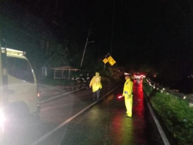 Petugas kepolisian di saat mengatur lalin dikawasan jalan yang tertimbun longsor