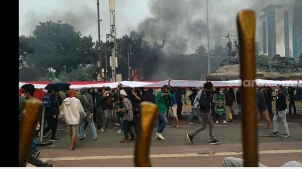 Bendara Merah Putih dibentangkan pendemo saat bentrok dengan aparat di kawasan Patung Kuda, dekat Istana Negara.