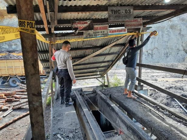 Polisi Saat Memasang Garis Polisi di Lubang Tambang Tahiti Coal