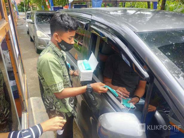 Petugas memberikan masker kepada pengunjung Pantai Air Manis Padang