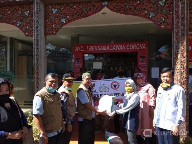 Kepala Pelaksana Harian UPZ Baznas Semen Padang Muhammad Arif (kanan) menyerahkan bantuan sembako berupa 10 kg beras kepada maayarakat yang diwakili oleh salah seorang Lurah di Lubuk Kilangan.