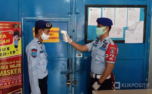 Petugas Lapas Kelas III Talu saat melakukan pengecekan suhu tubuh ketika hendak masuk