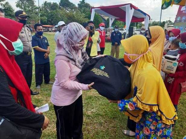 Ketua TP PKK Kabupaten Dharmasraya, Ny. Dewi Sutan Riska menyerahkan bantuan kepada salah seorang masyarakat saat mengikuti GERMAS di Kecamatan Sungai Rumbai.