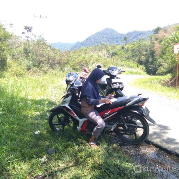 Seorang siswa di Palupuah Agam mencari sinyal ke perbukita untuk belajar daring