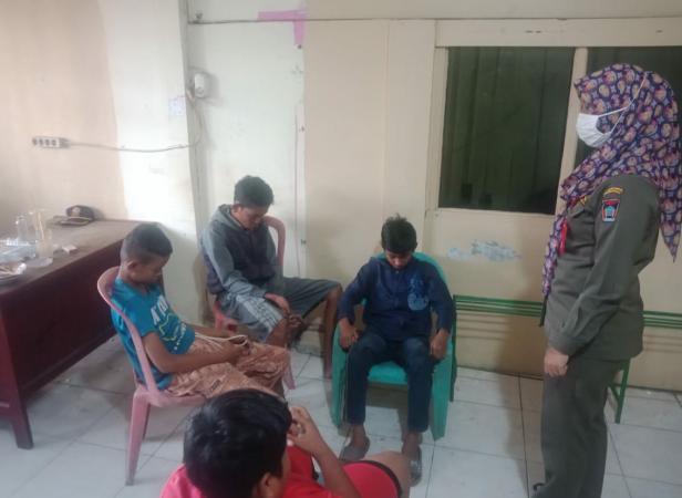 Seorang personel Satpol PP Padang memberikan arahan kepada empat remaja yang diduga mengganggu ketentraman dan ketertiban umum