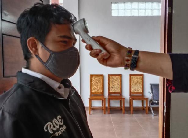Salah satu peserta harus diperiksa suhu badannya dengan thermogun sebelum mengikuti ujian Pra ALB  yang digelar Pengda INI Tanah Datar
