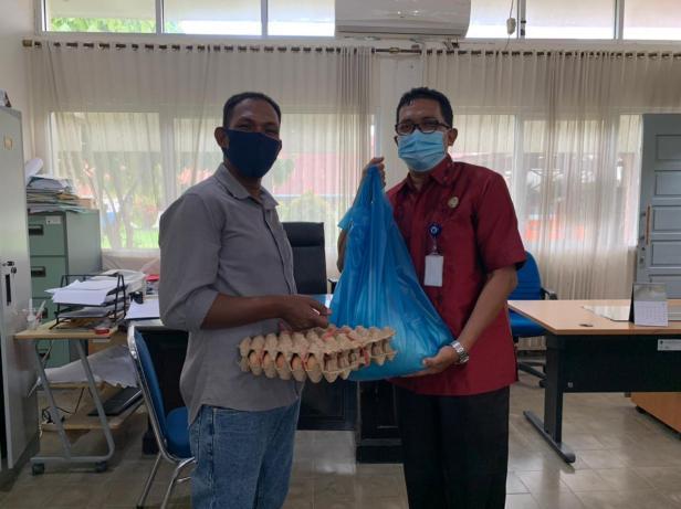 Kepala Bidang Perdagangan Disperindag Sumbar Ridonald (kanan) menyerahkan bantuan sembako gratis dari UPZ Baznas Semen Padang kepada masyarakat, Kamis (6/5/2021)