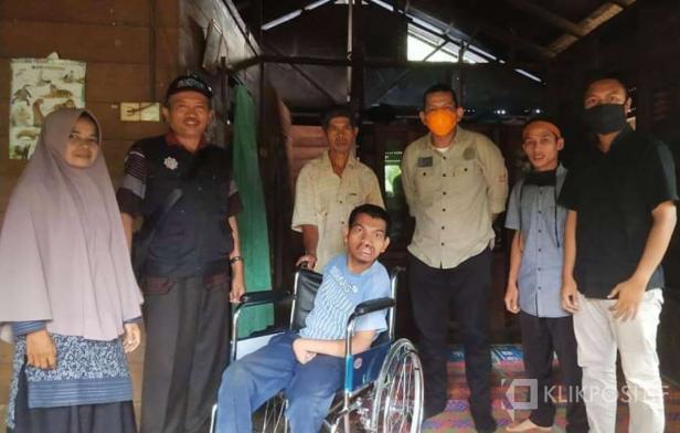 Guru Mon Eferi (bertopi) bersama Ketua Kolaboraksi Kemanusiaan Pasaman Barat, Decky H Saputra saat menyerahkan bantuan kursi roda dari sumbangan umat