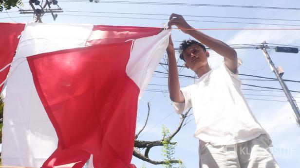 Seorang pedagang bendera di Jalan Sawahan sedang memajang bendera yang ia jual