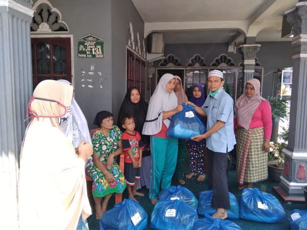 Petugas UPZ Baznas Semen Padang Ustad Mafril menyerahkan secara simbolis bantuan dari ibu-ibu kompleks PTSP kepada masyarakat kurang mampu yang tinggal di lingkungan perusahaan.