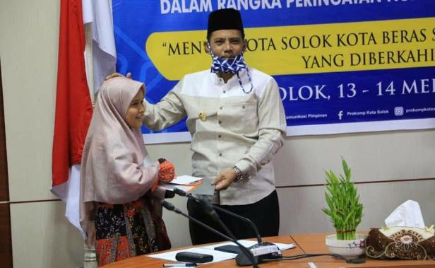 Ketua LPTQ Kota Solok, Reinier menyerahkan hadiah kepada pemenang lomba MTQ Virtual kota Solok.