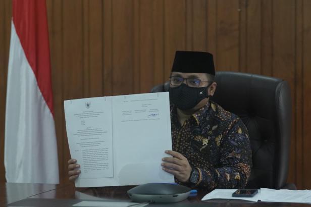 Menag Yaqut Cholil menunjukkan dokumen SKB 3 Menteri yang telah ditandatangani, Rabu (03/02)