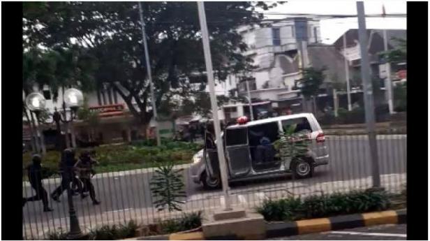 Tangkap layar video mobil ambulans berjalan mundur saat ditembaki polisi dengan gas air mata.