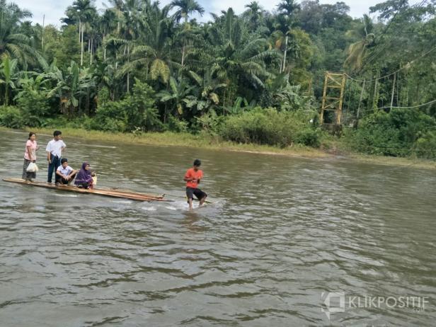 Beberapa orang dan siswa SMP saat diatas rakit menyebarangi sungai Ganting Kubang-Pessel