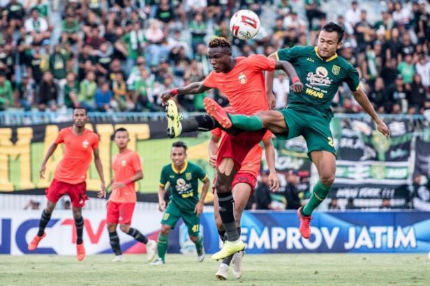 Arif Satria, pemain belakang Persebaya yang pernah berseragam Semen Padang FC berduel dengan pemain Bhayangkara FC.