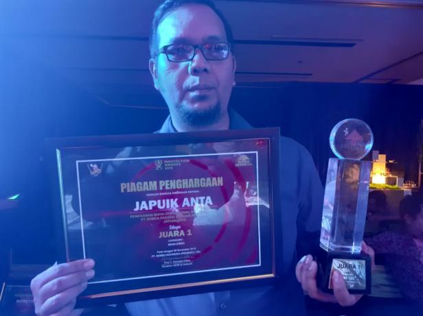 Salah satu perancang aplikasi JPA,  Firma Yudi, memegang piala dan piagam penghargaan pada  ajang Innovation Award SIG 2019.