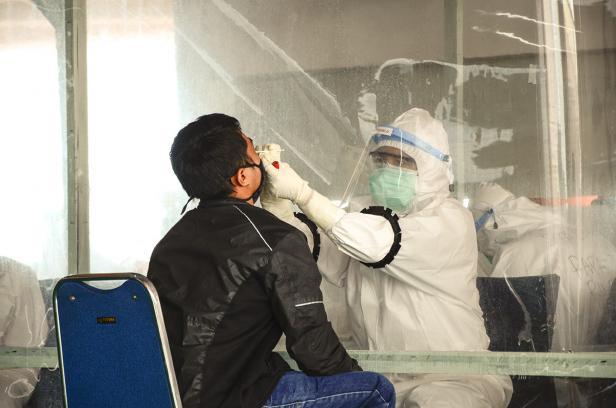 Petugas melakukan pengambilan sampel untuk tes swab