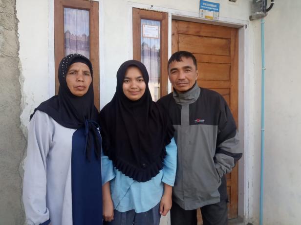 Adinda Aisyah Rahman (tengah) berfoto bersama kedua orangtuanya di halaman rumahnya di Alahan Panjang.
