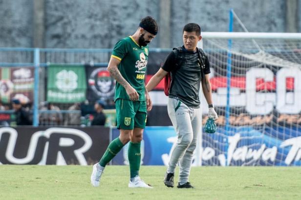 Gelandang bertahan Aryn Glen Williams didampingi dokter tim Persebaya dr. Pratama Wicaksana Wijaya keluar lapangan.