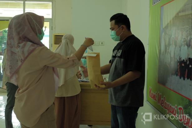 Seorang petugas di tempat karantina memasukkan surat suara ke dalam amplop yang dijadikan sebagai kotak suara