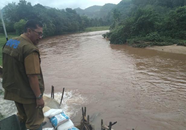 Kepala BPBD Limapuluh Kota, Joni Amir memantau air sungai yang mulai naik.