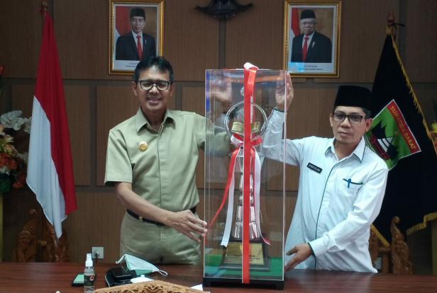 Gubernur Sumbar Irwan Prayitno bersama Kabiro Bintal Syaifullah memegang piala juara umum