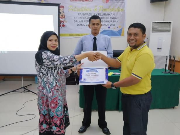 Anggita Panwascam Lubuk Kilangan Vita Martasari memberikan piagam penghargaan kepada anggota Panwas Kelurahan Bandar Buat, Eko Yuhedi yang menjadi peserta pembekalan terbaik.