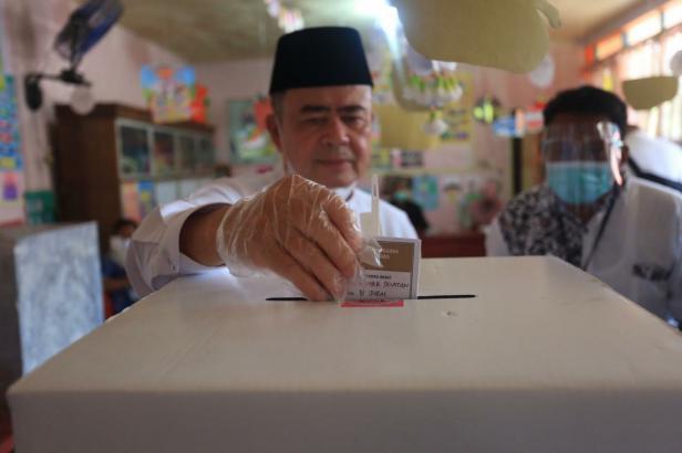Calon gubernur Sumatera Barat (Sumbar) Nasrul Abit bersama istrinya Wartawati Nasrul Abit telah selesai mencoblos di 006 Painan Timur Painan IV Jurai Kabupaten Pesisir Selatan