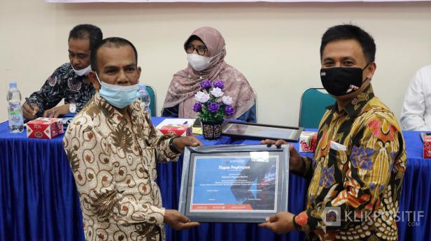 Direktur Utama KlikPositif Oktaveri serahkan piagam penghargaan kepada Jhon Hendri dari Koperasi Pegawai madina dalam anugerah Klik Award yang dilaksanakan di Kampus Universitas Fort de Kock Bukittinggi, Jumat 9 April 2021.