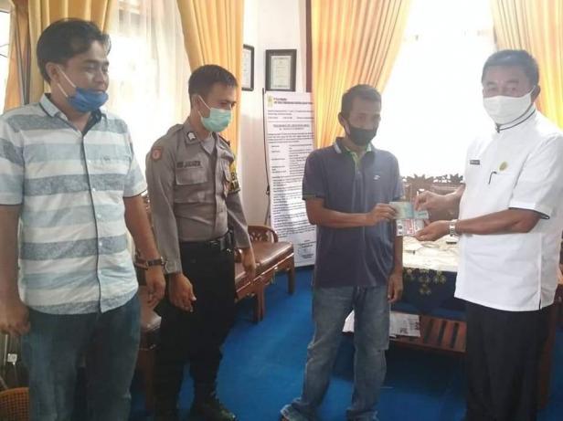 Seorang warga Nagari Sungai Rumbai mengembalikan Bantuan Lansung Tunai (BLT) dampak COVID-19 kepada pihak nagari yang diterima lansung wali nagari Sungai Rumbai Rasul Hamidi Dt Saridano.