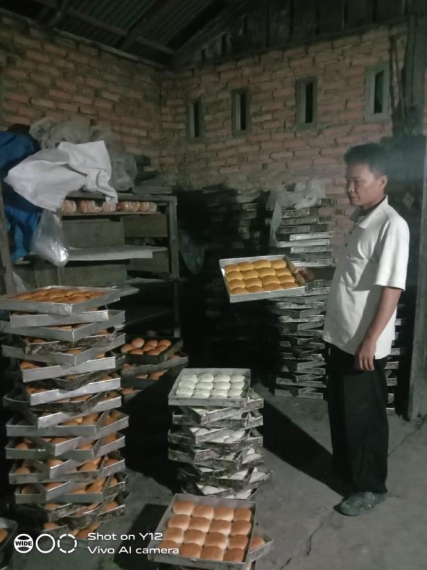 Amrizal memegang roti hasil produksinya. Usahanya tetap bertahan di tengah pandemi.
