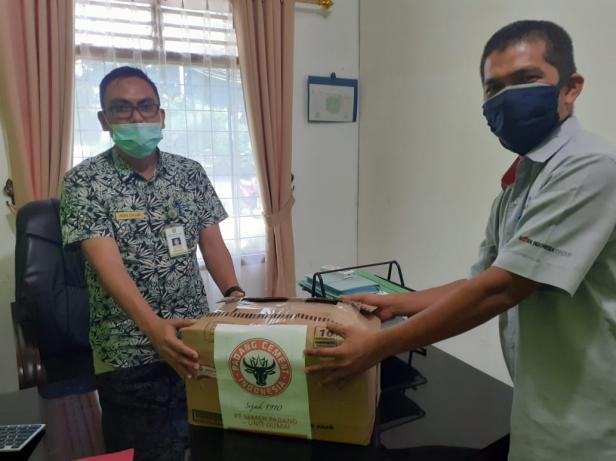 BANTUAN MASKER: Senior Manager PT Semen Padang Pabrik Dumai Palman (kanan) menyerahkan bantuan sebanyak 500 pcs masker kepada Sekretaris Dinas Lingkungan Hidup Kota Dumai Indra Safawi pada Kamis, 2 Juli 2020.