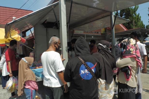 Seorang pedagang di Pasar Murah Pemko Padang melayani pembeli.