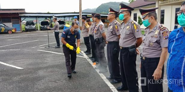 Salah seorang petugas tengah menyemprotkan disinfektan kepada personil Polres 50 Kota saat apel pagi.