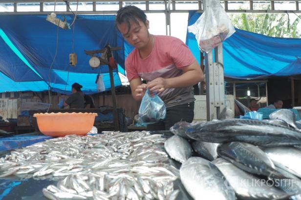 Jufrian memasukkan ikan ke dalam kantong dan memberikannya kepada pembeli di Pasar Raya Padang.