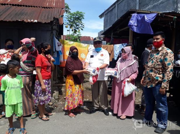 Martias, anggota DPRD Pasaman Saat membagikan paket sembako dan masker kepada warga