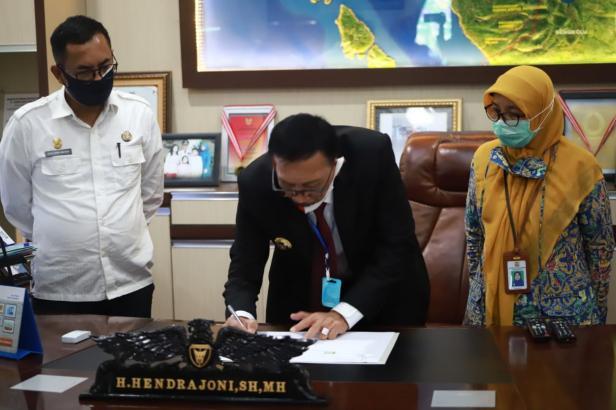 Bupati Pessel Hendrajoni saat menandatangani nota pembangunan jalan desa, serta hak pengelolaan jaringan perpipaan Sistem Penyediaan Air Minum (SPAM) Kepala Balai Prasarana Permukiman Wilayah Provinsi Sumatera Barat, Syafriyanti.