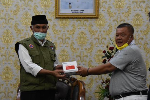 Rukiat Sabit, mewakili Ketua Yayasan Buddha Tzu Chi Perwakilan Kota Padang Widya Kesuma menyerahkan secara simbolis bantuan rapid test kepada Wali Kota Padang Mahyeldi