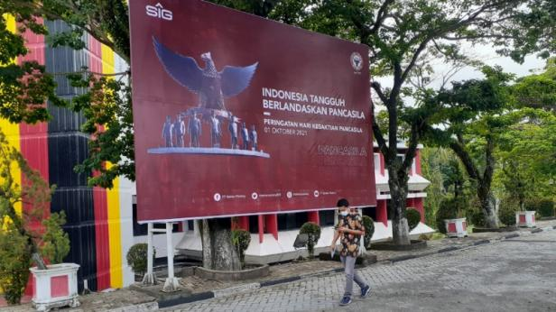 Seorang pria berjalan di depan Baliho peringatan Hari Kesaktian Pancasila yang dipasang di Plaza Kantor Pusat PT Semen Padang, Jumat (1/10/2021). Manajemen PT Semen Padang mengajak seluruh karyawan Semen Padang Group untuk mengibarkan bendera setengah tiang pada tanggal 30 September dan bendera satu
