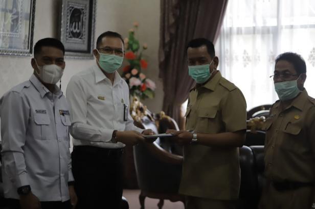 Bupati Pessel, Rusma Yul Anwar saat menerima simbolis bantuan melalui Kasatker Perumahan Sumbar, Syamsul di Rumdin Bupati